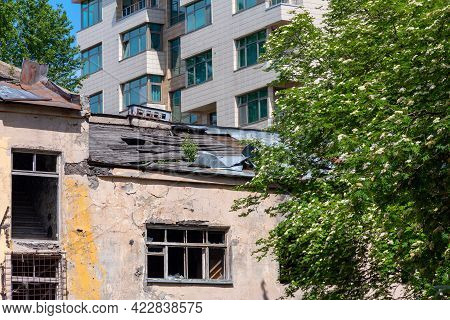 An Old Abandoned House And A New Tenement Comfortable Building. Urban Contrasts And Territorial Deve