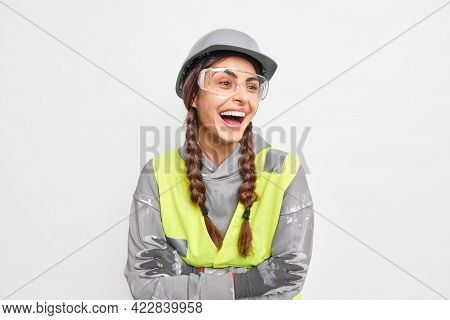 Positive Carefree Woman Engineer Laughs Happily Keeps Arms Folded Looks Away Satisfied With Quick Co