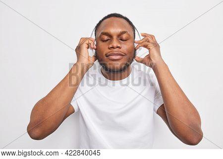 Indoor Shot Of Dark Skinned Man Closes Eyes Enjoys Listening Favorite Lyrics Song Wears Wireless Hea
