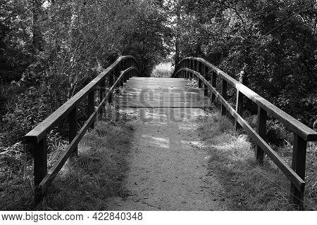 Black And White Of A Small Romantic Wooden Bridge Over A Small River
