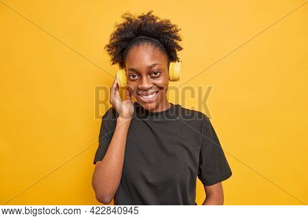 Portrait Of Beautiful Thin African American Woman Listens Music Via Wireless Headphones Looks With G