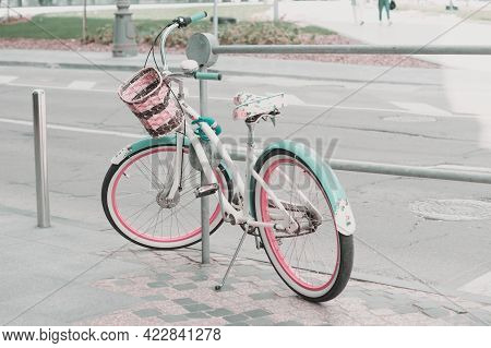 Women's Bicycle Parked On The Street With A Lock. Vintage Bicycle In Mint And Pink Colors With A Bas