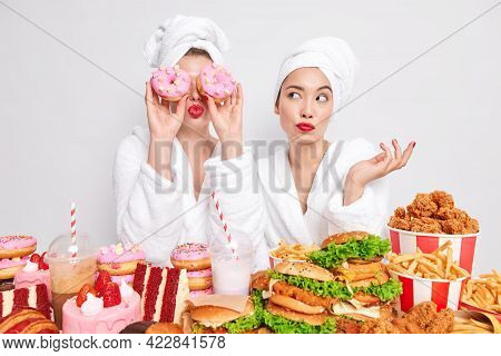 Unhealthy Lifestyle And Junk Food Concept. Two Women Pose Near Table Full Of Delicious Appetizing Sn