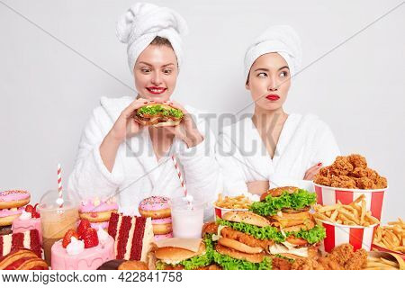 Positive Woman Looks With Temptation At Delicious Hamburger Starves For Eating It Consumes Burgers F