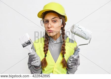 Horizontal Shot Of Attentive Female Builder Holds Painting Brush And Roller Ready For House Refurbis