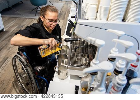 Minsk, Belarus - January, 2021: Wheelchair Disabled Person Works As A Barista In An Inclusive Coffee