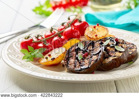 Grilled Eggplant Steaks Are Served With Potatoes, Cherry Tomatoes And Balsamic Sauce. Less Meat Conc
