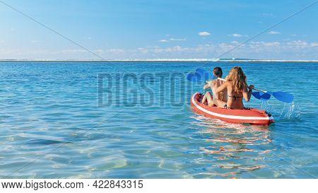 Young Women Have Fun On Boat Walk. Girls Paddling On Kayak By Sea Lagoon. Travel Lifestyle, Recreati