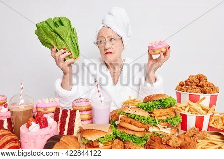 Pensive Old Woman Chooses Between Healthy And Unhealthy Food Holds Green Salad And Tasty Delicious D