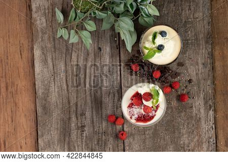 Top view of raspberry Panna Cotta and chocolate mousse isolated on the wooden table