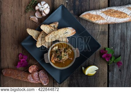 Top view of Gambas Pil Pil - Sizzling prawns with chili and garlic served with bread on the side isolated on wooden rustic table