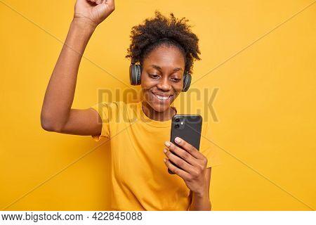 Overjoyed Dark Skinned Female Model Raises Arm Feels Very Happy Focused At Smartphone Listens Music