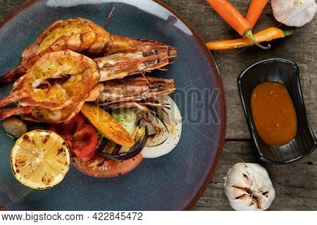 Wok-fried prawns with garlic and chili isolated on wooden rustic table