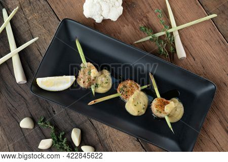 A skewer of seared hokkaido scallops with lemongrass flavouring served with curry cauliflower sauce isolated on wooden table