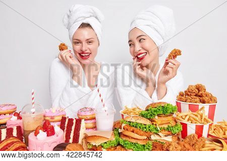 Happy Mixed Race Young Women Look Gladfully At Each Other Eat Junk Food Hold Nuggets Have Tasty Dinn