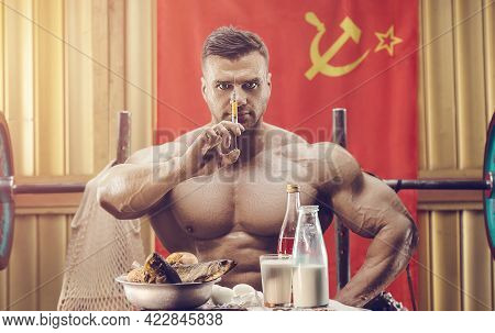 Old Fashion Bodybuilder Doing Exercises In Old School Gym With Ussr Flag. Handsome Caucasian Sports
