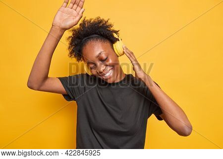Studio Shot Of Happy Black Woman With Natural Curly Hair Dances To Music Keeps Arm Raised Listens Fa