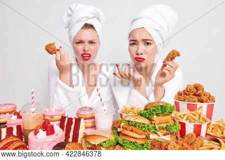 Displeased Indignant Young Women Look Unhappily At Camera Hold Chicken Nuggets Eat Fast Food Have Ba