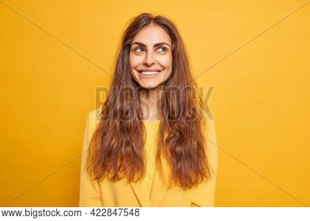 Portrait Of Good Looking Brunette Young Woman Smiles Gently Has Dreamy Expression Thinks About Somet