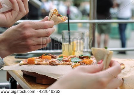 Close-up Of Hands And Pizza With Basil Leaves In An Outdoor Street Cafe. People Eat Pizza With Their