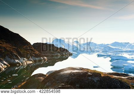 Iceberg In The Ilulissat Icefjord, West Coast Of Greenland. Rocky Coast With Calm Water And Reflecti