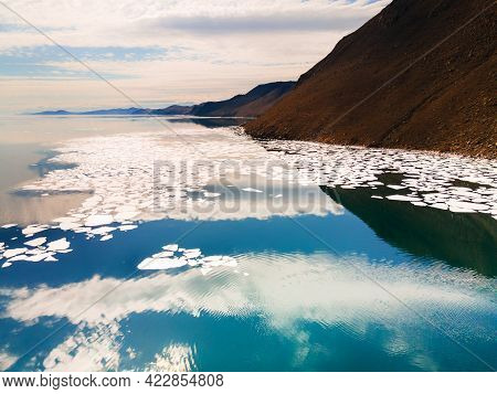 Melting Ice Floes On The Shore Of Baikal Lake In Spring. Aerial Drone View. Mountains And Sky Are Re