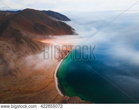 Fog Over The Shore Of Baikal Lake And Mountains. Aerial Drone View. Baikal Lake, Siberia, Russia. Be
