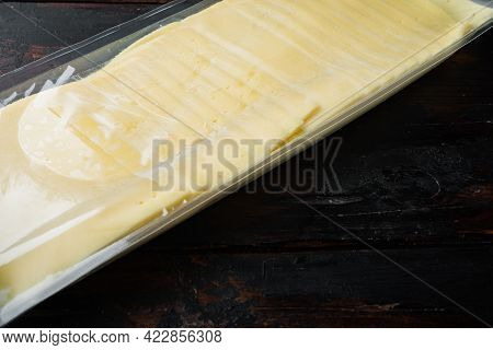 Cheddar Cheese In Vacuum Pack, On Dark Wooden Background With Copy Space For Text
