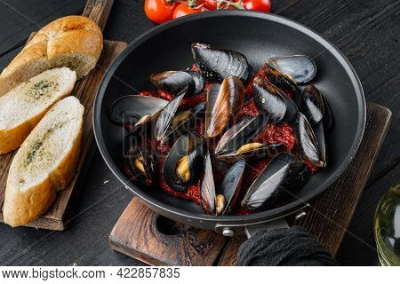 Mussels Grilled With Tomatoe Sauce With Herbs, On Frying Iron Pan, On Black Wooden Table Background