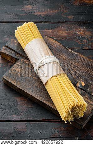 Spaghetti Italian Traditional Cuisine, Dry And Uncooked Set, On Wooden Cutting Board, On Old Dark  W