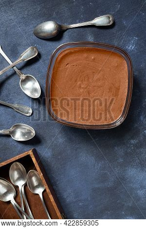A Bowl With Traditional French Chocolate Mousse And Silver Spoons On Blue Background And In The Box,