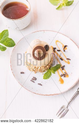 Caramel Coffee Cake In A Glaze With Nuts On Plate Over White Background, Top View