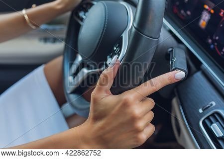 Womans Hand Switches The Lobes Of The Gear Selector On The Steering Wheel. Hand Is Switching Car Gea