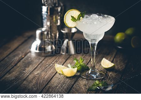 Cocktail Margarita Garnished With Lime And Mint On Wooden Background