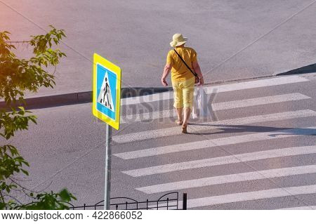 A Woman Crosses The Road At A Pedestrian Crossing. Top View