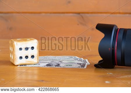 Homemade Dice And Dollar Bills Lie On A Wooden Table In Front Of A Camera Lens, Photographers Earnin