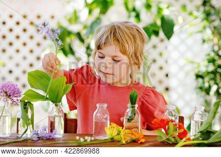 Little Preschool Girl Making Flower Bouquet At Home. Toddler Child Putting Colorful Garden Summer Fl