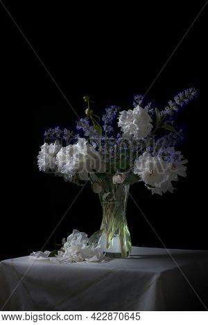 Classic Still Life With A Beautiful Bouquet Of White And Purple Peony And Sage Flowers In An Antique