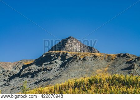 Scenic Alpine Landscape With Sharp Rock Pinnacle And Snow-covered Mountain In Sunlight In Autumn. Mo