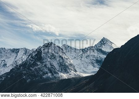 Great View To High Snowy Mountain Wall With Peaked Top Under Cirrus Clouds In Sky. Alpine Landscape