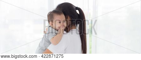 Young Asian Mother Holding Little Baby Girl And Walking Together In The Bedroom At Home, Mom Carry D