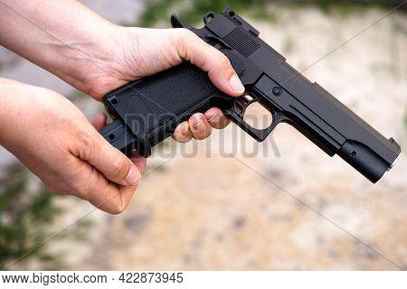 A Person Reloading An Airsoft Gun. Close-up