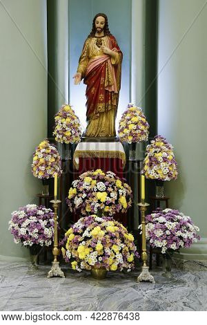 Sacred Heart Of Jesus On A Decorated And Flowered Altar