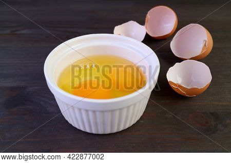 Vibrant Color Raw Eggs In A Bowl With Cracked Eggshells In The Backdrop