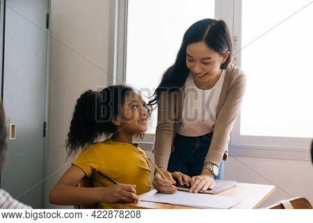Asian School Teacher Assisting Female Student In Classroom. Young Woman Working In School Helping Gi