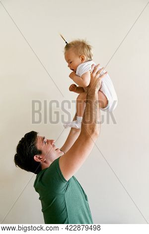 Daddy Raises The Little Girl Above His Head