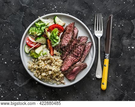 Delicious Lunch - Bulgur, Lettuce, Cucumber, Tomato Salad And Steak On A Dark Background, Top View