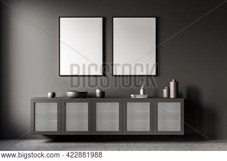 Grey Art Room Interior With Long Wooden Commode With Books And Vase On Concrete Floor. Two Blank Fra