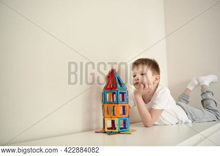 Boy Dreamig About Space, Playing In A Magnetic Bright Multicolored Constructor. A Schoolboy Makes A
