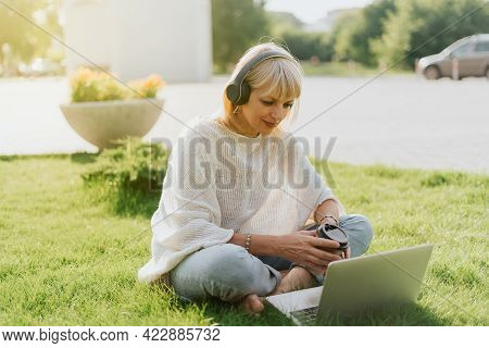Mature Adult Woman In Headphones Using Laptop, Sitting On The Grass Outside In Park. Happy And Smili
